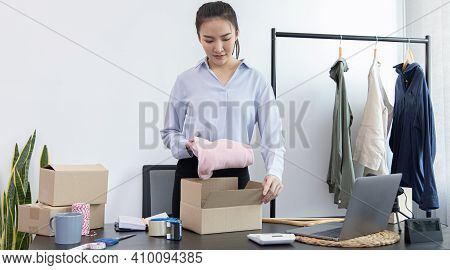Young Asian women pack their clothes into boxes and prepare them to be delivered by post, Online clo