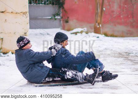 Baku, Azerbaijan .2.02.2014. Two Very Happy Caucasian Kids Playing In The Snow A Sled . Boys Sleddin