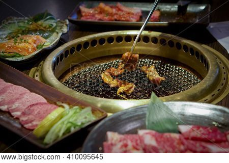 Japanese Barbecue On A Hot Chacoal Stove. Chicken Grilling On Griddle Pan.