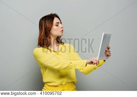 Serious Woman In Yellow Blouse Using Digital Tablet With Blank Screen On Grey.