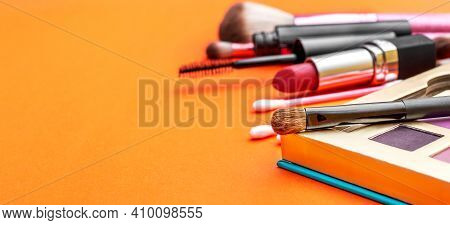 Makeup Accessories On A Bright Orange Background.