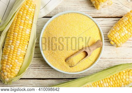 Cornmeal In Bowl And Fresh Cobs On White Wooden Table, Flat Lay