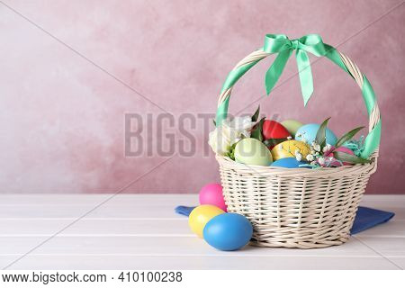 Wicker Basket With Bright Painted Easter Eggs And Flowers On White Wooden Table Against Pink Backgro