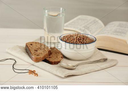 Cross, Buckwheat Porridge, Bread, Glass Of Water And Bible On White Wooden Table. Lent Season