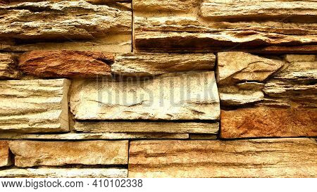 Stone Wall, Close-up. A Traditional Stone Wall Made Of Rectangular Stones Of Different Sizes In Brig
