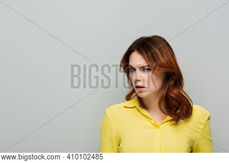 Distrustful Woman In Yellow Blouse Looking At Camera Isolated On Grey.
