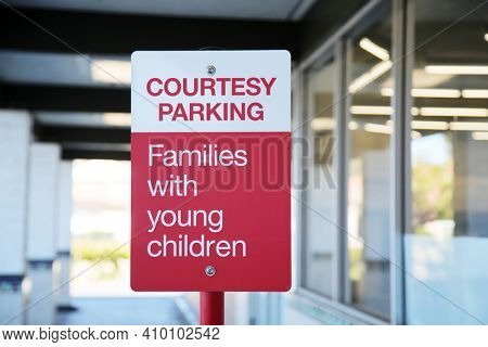 Parking Sign. Courtesy Parking - Families with young children. Red and White Courtesy Parking Sign.