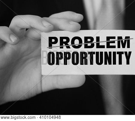 Businessman Holding A Card With Word Problem Strikeout And Opportunity. Problem Turns Into Opportuni