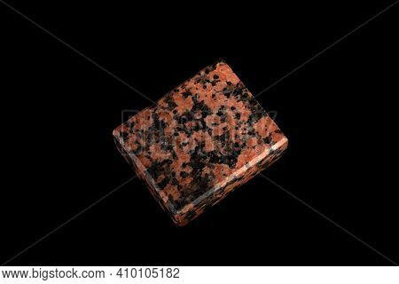 Closeup Of A Specimen Of Natural Stone Red Granite Mineral Stone On Black Glass. A Polished Piece Of