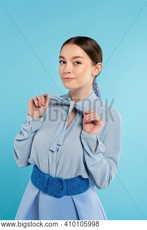Elegant Woman Touching Bow On Blouse While Smiling At Camera Isolated On Blue