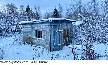 An Old Wooden Building In The Middle Of A Snowy Forest. Ruined Small House In Winter.