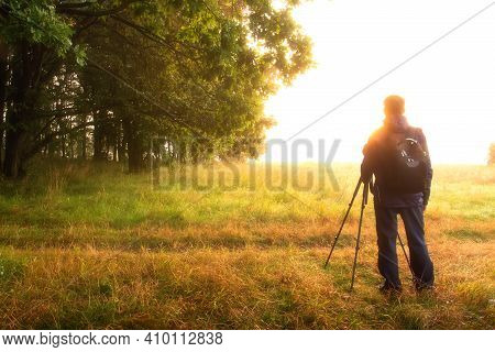A Man Dreams Against Vivid Sunrise In The Spring Morning. Photographer With Tripod Enjoys The Beauti