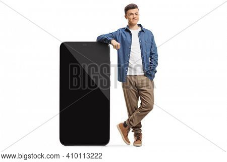 Full length portrait of a casual guy leaning on a big smartphone isolated on white background