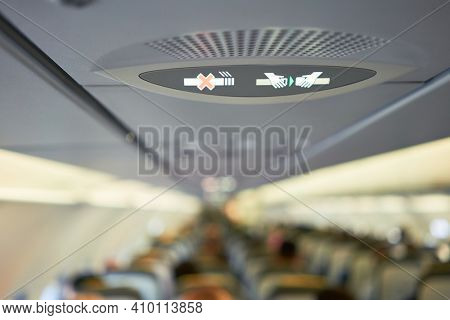 Passengers and crew sitting on airplane seats, view of the passengers and attendants inside cabin