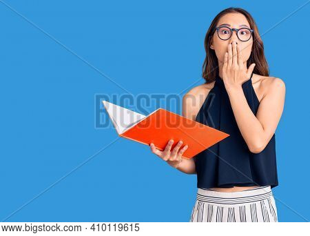 Young beautiful chinese girl holding book covering mouth with hand, shocked and afraid for mistake. surprised expression