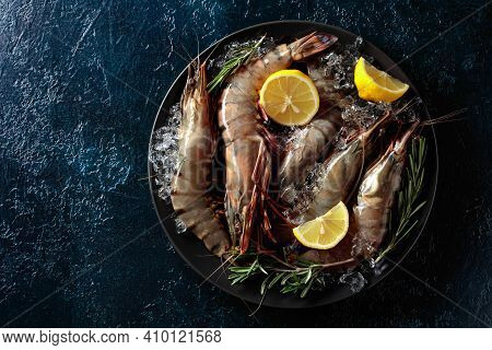 Fresh Tiger Prawns In A Black Plate With Lemon, Rosemary And Crushed Ice, Top View With Copy Space.
