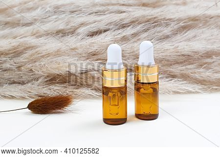 Two Bottles Of Hyaluronic Acid With Pipette And Brawn Herb Lagurus On Cortaderia Or Pampas Grass Bac