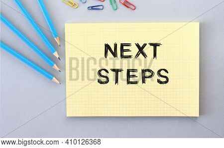 Next Steps Text In Notebook On Gray Background Next To Pencils And Paper Clips. Concept.