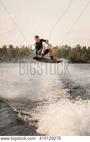 Young Sportive Guy Effectively Jumps On Wakeboard Over The Water