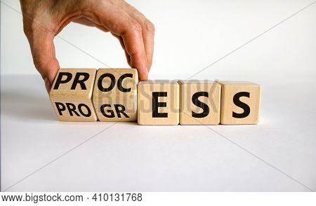 Process And Progress Symbol. Businessman Turns Wooden Cubes And Changes The Word 'process' To 'progr