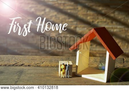 Selective Focus Of People Miniatures And Toy House With Text First Home.