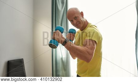 45 Year Old Athlete Trainer Exercising With Dumbbells. Trainer Standing At Home With Dumbbells In Hi