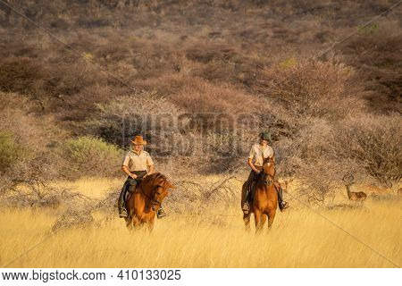 Two Women Riding Horses Watched By Impala
