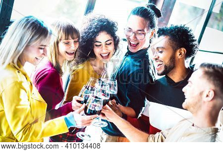 Young Multiracial People Drinking And Toasting Red Wine At Dinner Party - Happy Drunk Friends Having