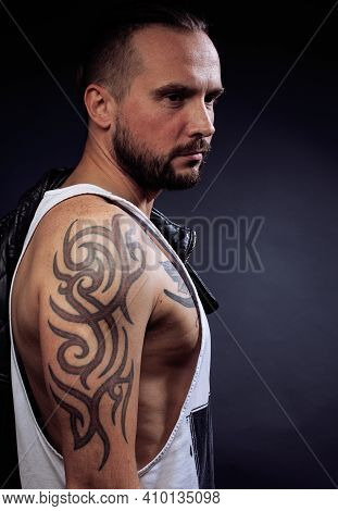 A Man With Tattooes On His Arms. Silhouette Of Muscular Body. Caucasian Brutal Hipster Guy With Mode