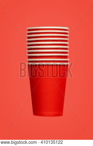Stack Of Ten Red Paper Eco-friendly Cups On Red Background. Empty Space. Environmental Problems Conc