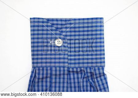 Cuff On The Sleeve Of A Shirt In A Cage Top View. Sleeve Of A Man's Shirt With A White Button On A W