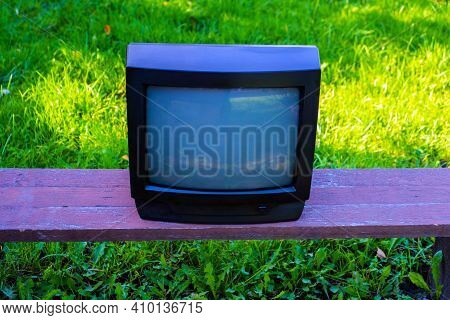 Old Analog Television Set On The Grass Background Outdoor