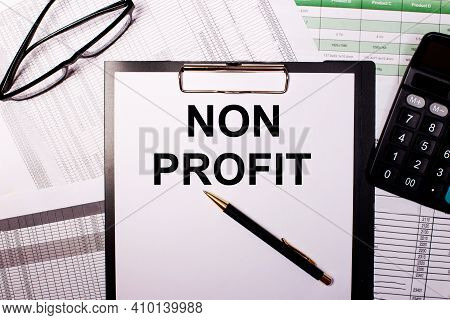 Non Profit Is Written On A White Sheet Of Paper, Near The Glasses And The Calculator.