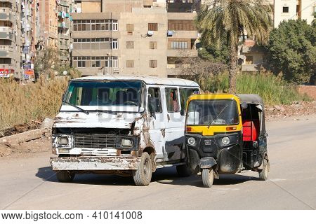 Cairo, Egypt - January 26, 2021: Old Urban Minibus Eltramco Ramzes And Tuk Tuk Bajaj Re In The City