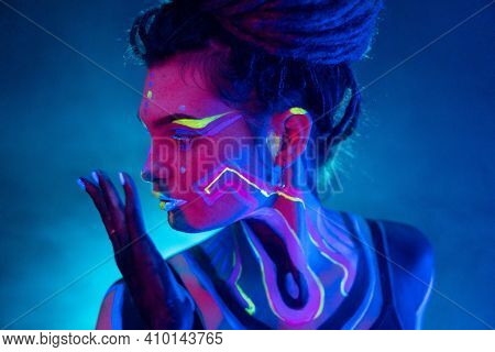 Cocky Girl With Dreadlocks In Ultraviolet Neon Light With Foggy Background. Bodyart