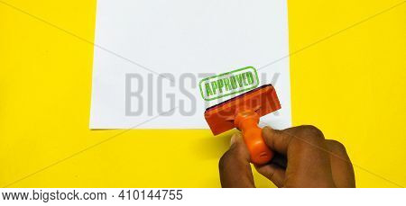 Closeup of a Approved stamp and a rubber stamp in a blank White paper with a selective focus on