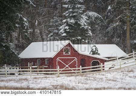 An Old Red Barn In A Winter Wonderland During A Snow Storm.