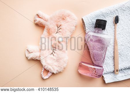 Tooth Care Concept. Mouth Rinse, Sleeping Mask And Toothbrush On Pink Background, Top View, Flat Lay