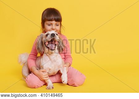 Little Girl With Dog Having Fun Together While Sitting On Floor, Small Kid Embracing Her Pet And Loo