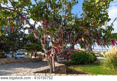 Protaras, Republic Of Cyprus - June 10. 2019. Tree With Colored Ribbons Of Wishes Near Church Of Pro