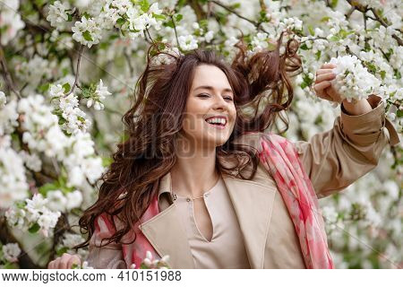 Portrait Of A Beautiful Smiling Brunette Young Women  In Blossom Apple Tree Garden In Spring Time. E