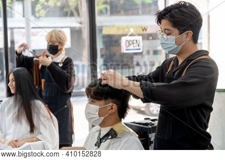 Beauty Salon Asian Barber Man With Hygiene Mask Work With Hair Of Customer In The Shop With Other Co