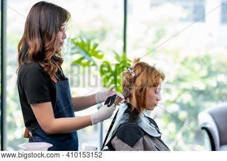 Beauty Salon Barber Woman Process Of Dyed Caucasian Woman Hair In The Shop, Both Of Them Wear Face S
