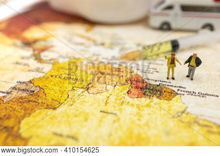 Miniature People Stand On World Map With Ambulance Car, Medical Mask And Syringe Of Covid-19 Vaccine