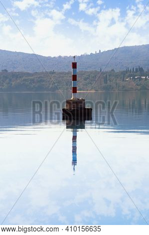 Beautiful Symmetrical Mediterranean Landscape. Striped White And Red Beacon On Water.  Montenegro, A