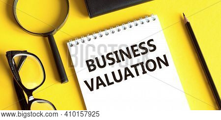 Notepad With The Text Business Valuation On A Yellow Background With Glasses, A Magnifying Glass And