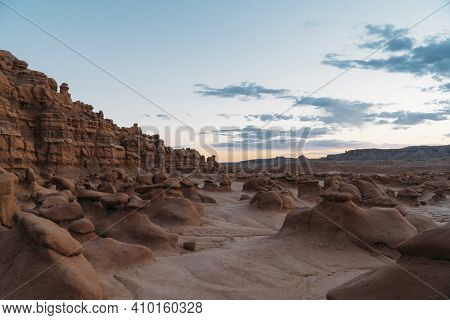 Red Mushroom Rocks In Goblin Valley State Park During Sunrise With Beautiful Orange And Purple Sky.