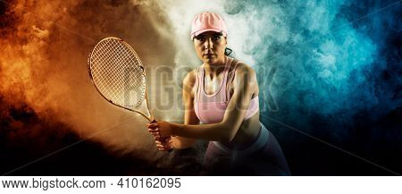 Female tennis player in action during game on smoke background. Sports banner. Horizontal copy space background
