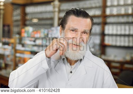 Happy Pharmacist. Close Up Portrait Of Smiling Handsome Senior Pharmacist Touching His Mustache, Sta