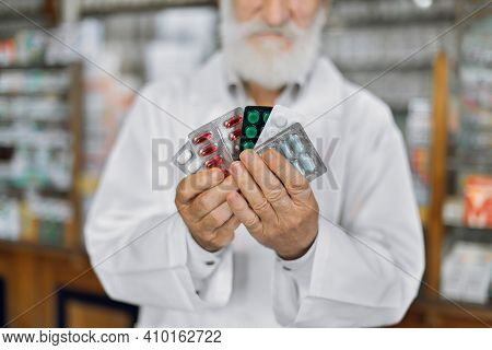 Closeup Of A Blurred Male Pharmacist Holding Out Tablets In Bottle At Drugstore Pharmacist Smiling A